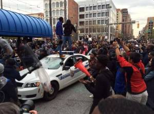 Rioters near Camden Yards in Baltimore smashing the windows and windshields of police cars.